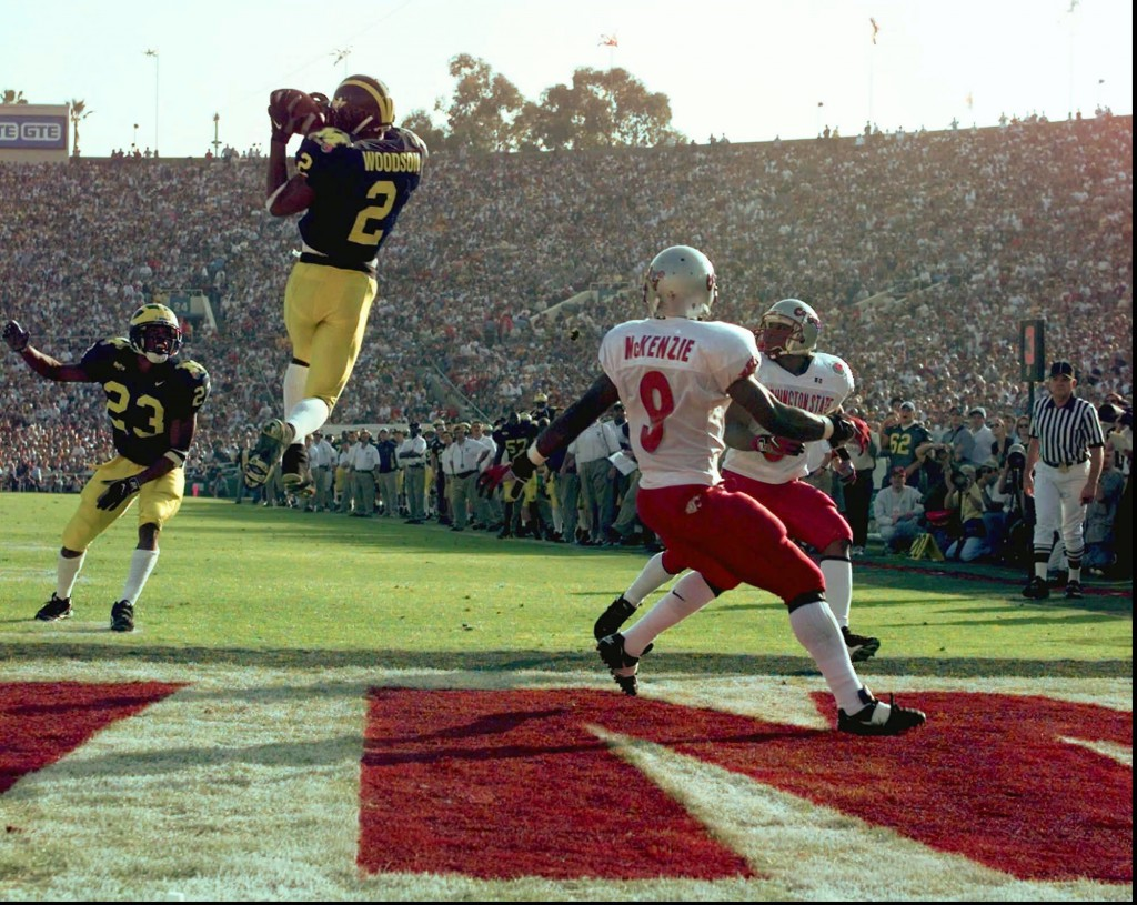 Michigan's cornerback Charles Woodson (2) leaps to make an interception in the end zone in the first half on a pass from Washington State's Ryan Leaf during the 84th Rose Bowl in Pasadena, Calif., Thursday, Jan. 1, 1998. Watching the play are Michigan's William Peterson (23) and Washington States Kevin McKenzie (9).